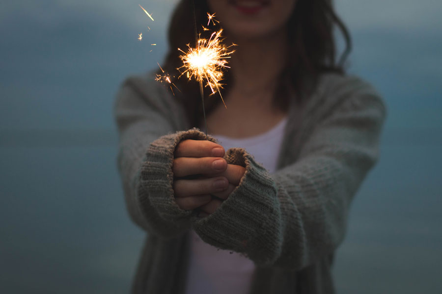 woman holding sparkler at dusk